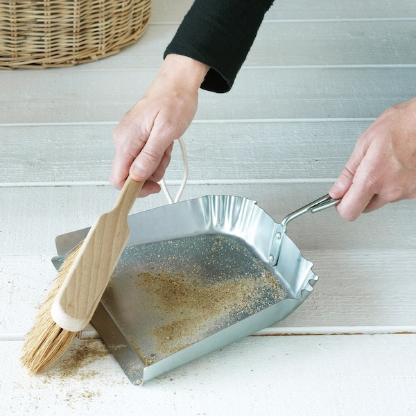 Galvanisierte Kehrschaufel mit Handbesen kehrt Schmutz vom Boden auf.