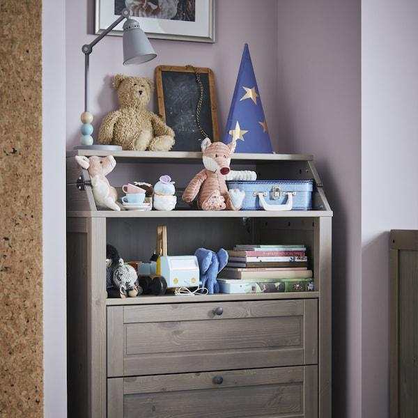Gambar unit meja menukar lampin/almari berlaci dengan mainan dan buku di atasnya.