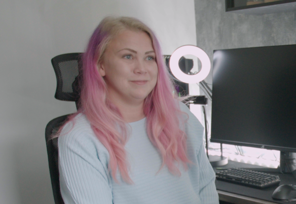 Gamer Sandra Östlund with pink hair and a light blue sweatshirt, sitting in front of a computer.