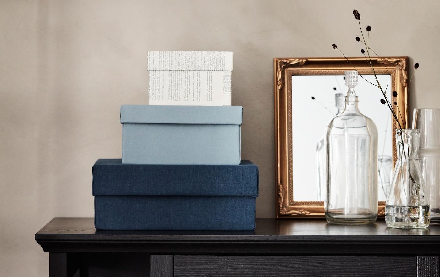 Gamle skobokse er forvandlet til nye opbevaringskasser beklædt med tekstiler og sider fra en gammel bog