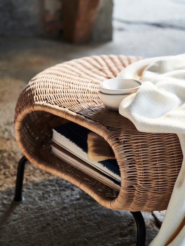 안에 책이 들어 있는 GAMLEHULT 감레훌트 풋스툴에 화이트 담요와 화이트 그릇 세 개가 놓여 있는 모습.