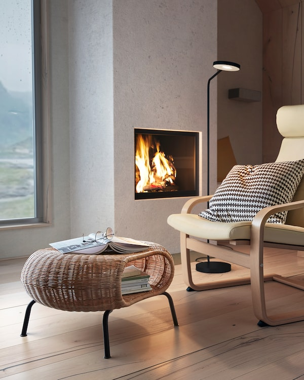 GAMLEHULT rattan footstool with hidden storage in front of an armchair, with an open fire and a floor lamp in the background.