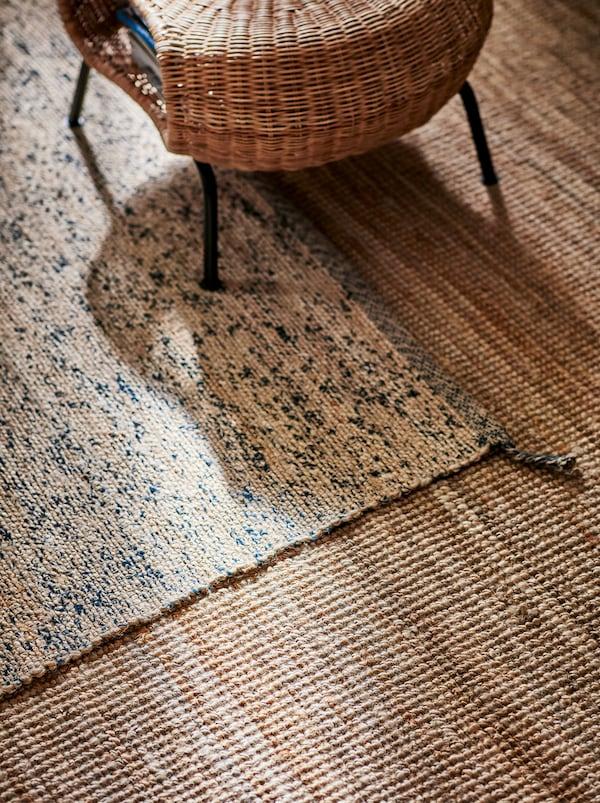 GAMLEHULT stoličica, pletena od ratana, na bež MELHOLT tepihu od jute, koji se nalazi na vrhu drugog, svetlobraon tepiha.