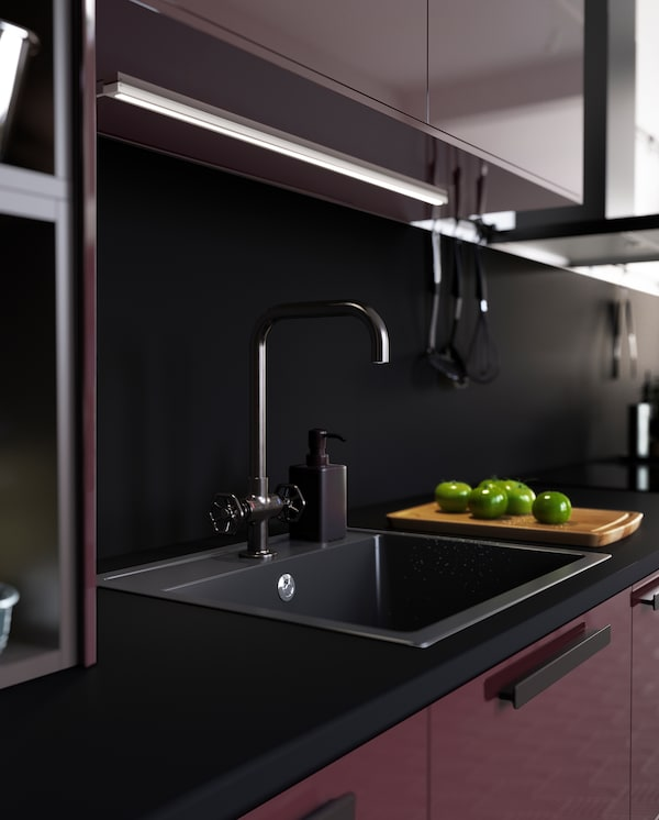 GAMLESJÖN dual-control kitchen mixer tap in brushed black metal and a black sink create a bold and coordinated expression.