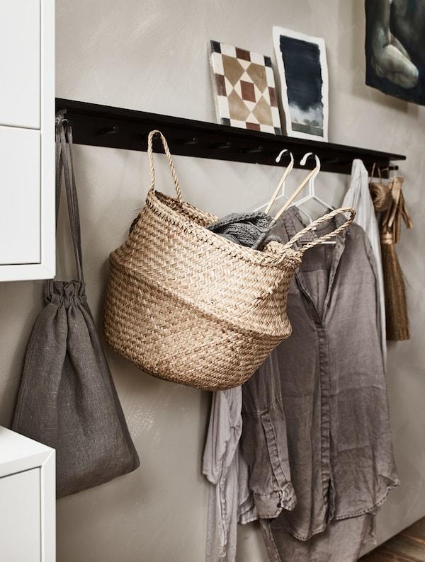 Ganchos de pared con ropa en perchas y una cesta.