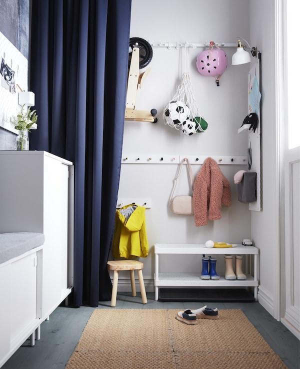 Ganchos de pared, un banco para zapatos y un taburete en este recibidor crean un almacenaje para niños que puede ocultarse detrás de una cortina azul.