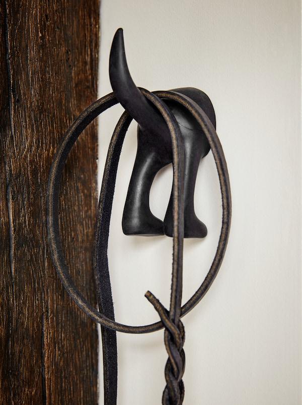 Gancio BÄSTIS nero a forma di coda di cane, a cui è appeso un guinzaglio.
