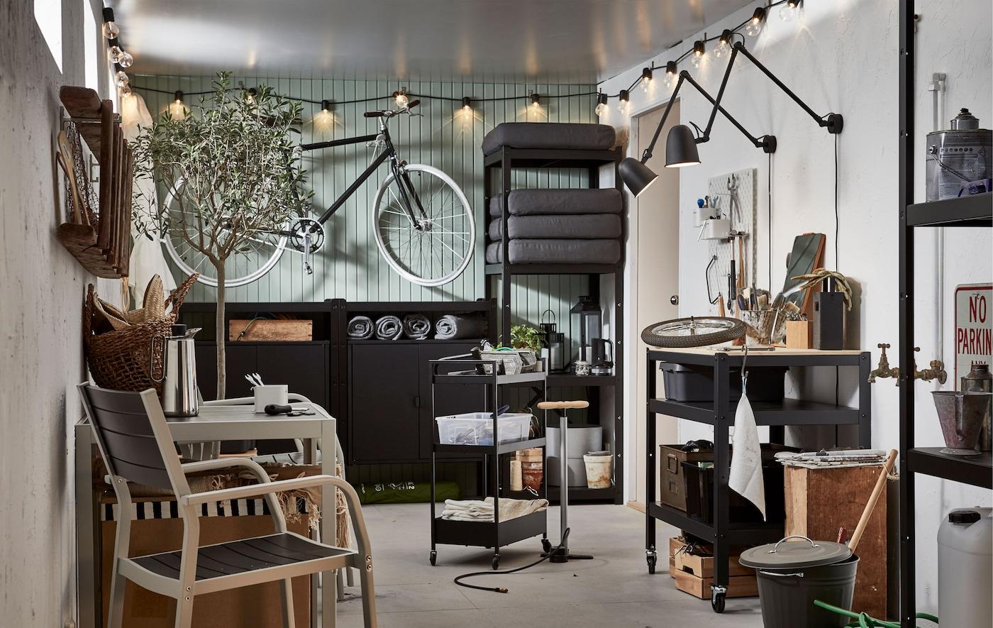 Garagelignende rum med en cykel hængt op på væggen, reoler med udendørsting, en stol, kaffe, stemningsbelysning og funktionel belysning.