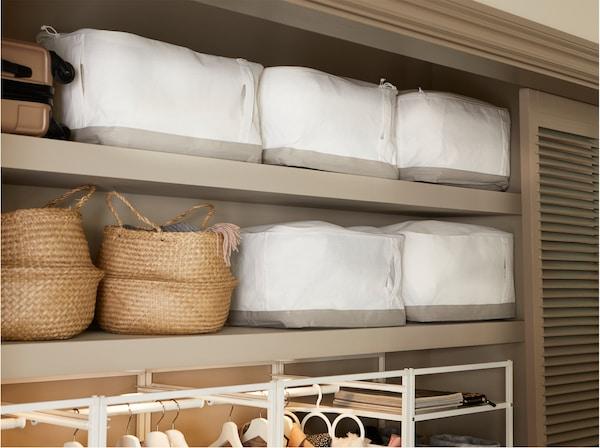 Garde-robe intégrée dans une entrée avec boîtes à compartiments IKEA LACKISAR blanches disposées sur les tablettes du haut à côté de paniers en jonc de mer.