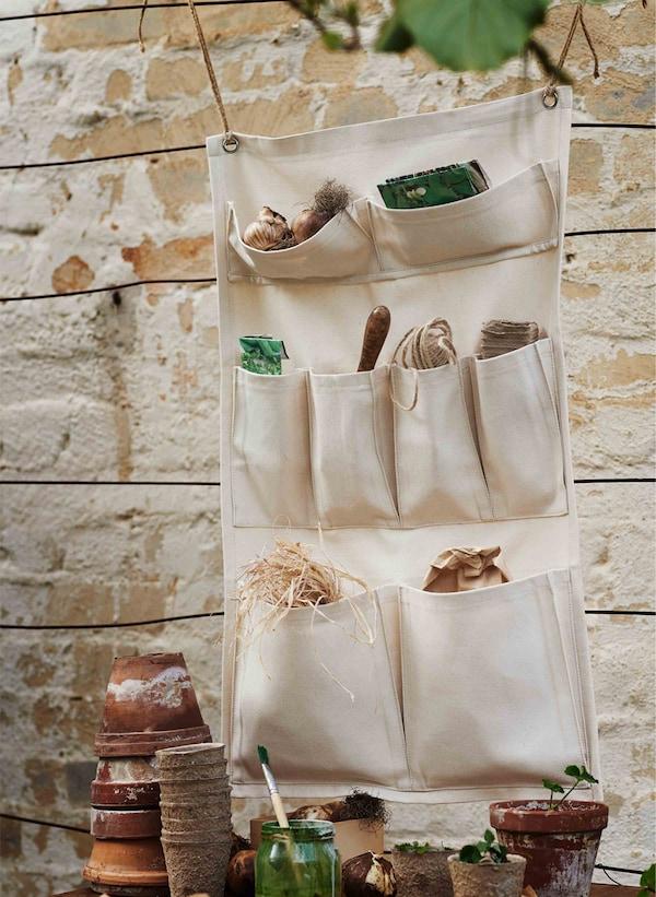 Gardening supplies sit within a cream-coloured wall organizer.