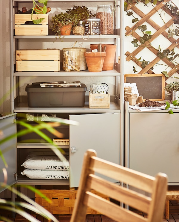 Gardening tools, supplies and potted plants sit in a shelving unit on a balcony.