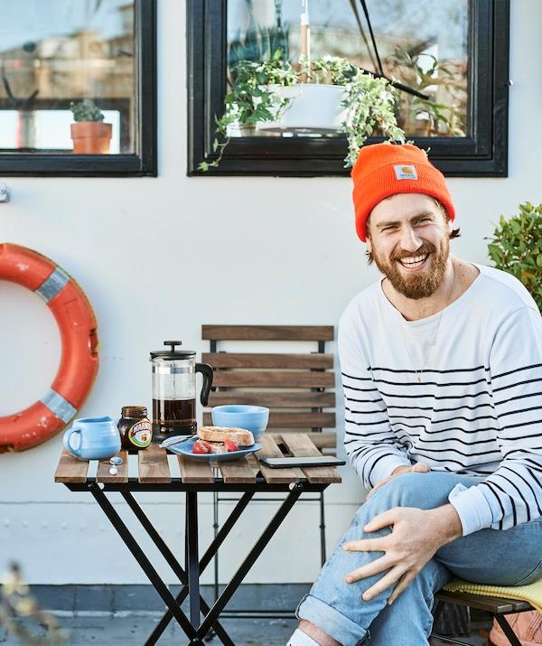Gareth sentado à mesa com o pequeno-almoço no exterior, na sua casa-barco.