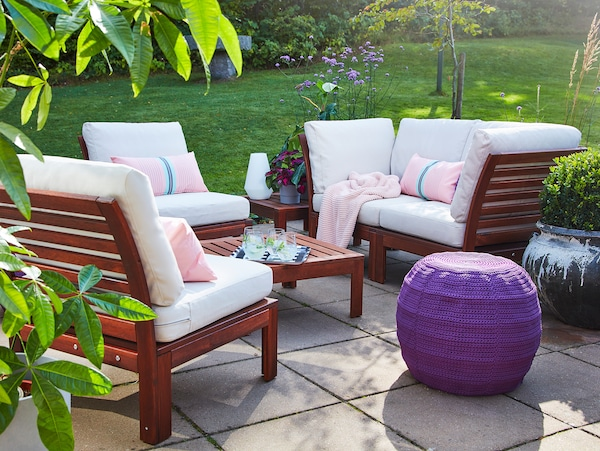 Garnitura s četiri sedišta i sto od bagrema, bež baštenski jastučići, ljubičasti tabure, roze ćebe i roze jastučići.