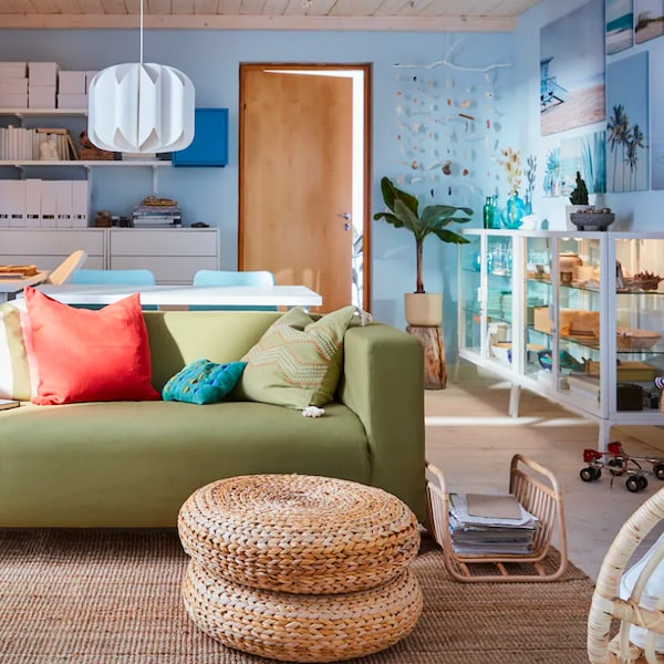 Garsonka ve které je obývací pokoj se zelenou sedací soupravou a jídlením stolem.