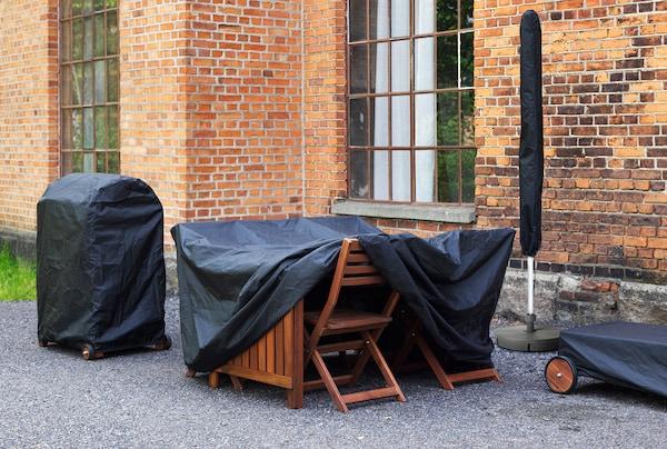 Gartenmöbel sind mit schwarzen Abdeckplanen & Schutzhüllen abgedeckt, um sie vor Regen zu schützen.