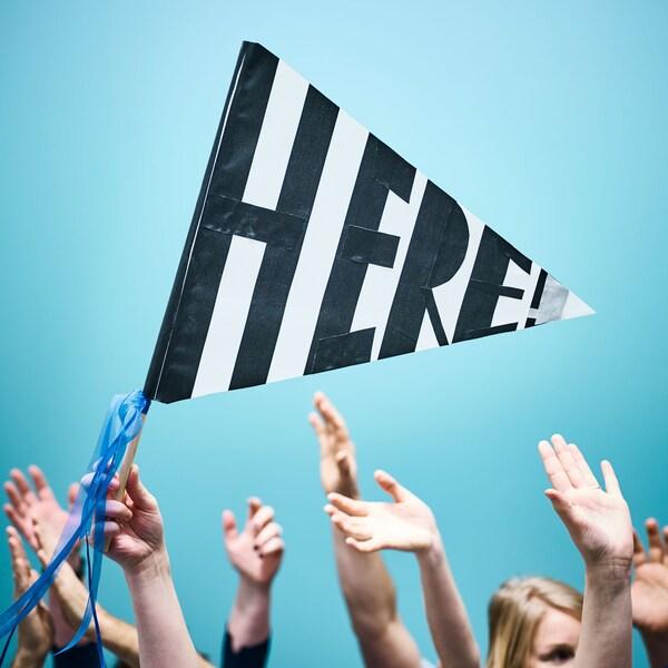 群衆が手を上げ、その中の一人が「here(ここ)」と書いた手づくりの旗を振っている