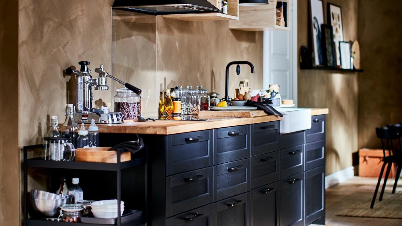 Gazdagon felszerelt konyhasarok kicsi, nyitott fali szekrényekkel, konyhai ventilátorral és sötét LERHYTTAN fiókfrontokkal.