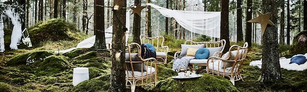 Gedekte tafel met stoelen, lichtsnoeren en ballonnen in de tuin