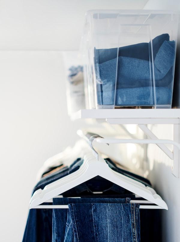 Gefaltete Kleidung in transparenten Boxen auf einem BERGSHULT Regal. Darunter hängt eine Reihe Kleidung an BUMERANG Kleiderbügeln.