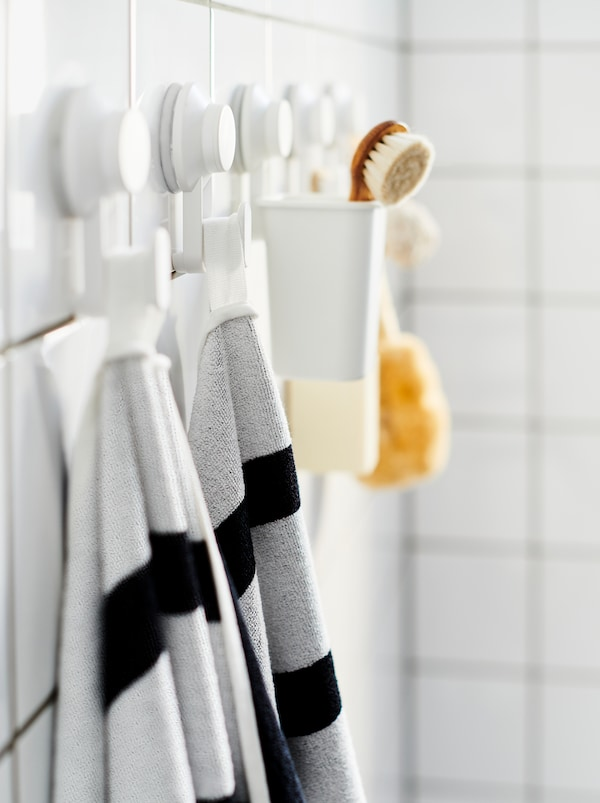 Geflieste Badezimmerwand mit einer Reihe TISKEN Haken mit Saugnapf, an denen Handtücher und Badutensilien befestigt sind.