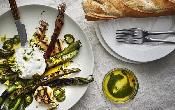 Gegrilltes Gemüse, Öl und Brot auf weißen Tellern