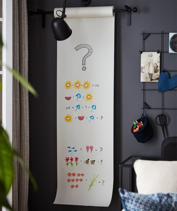 Gelaren izkinaren pareta marrazkiak dituen paper-biribilkiarekin dekoratuta dago, eta horren zati batek grafiko koloredunak eta matematika-problemak ditu.