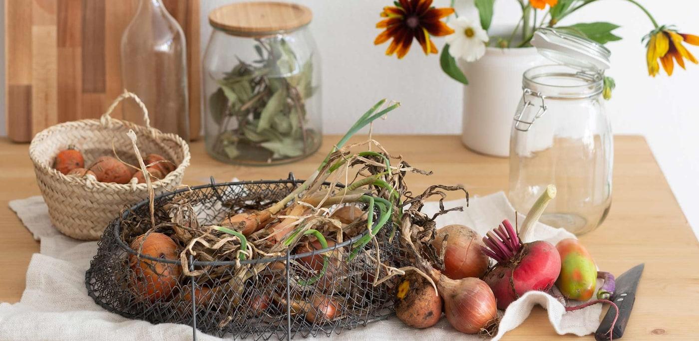 Gemüse auf einem Holztisch für die Fermentation. Im Hintergrund stehen Blumen in einer Vase.