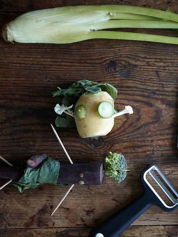 Gemüse, zu kleinen Figuren zusammengesetzt, umgeben u. a. von einem SMÅBIT Messer und Schäler
