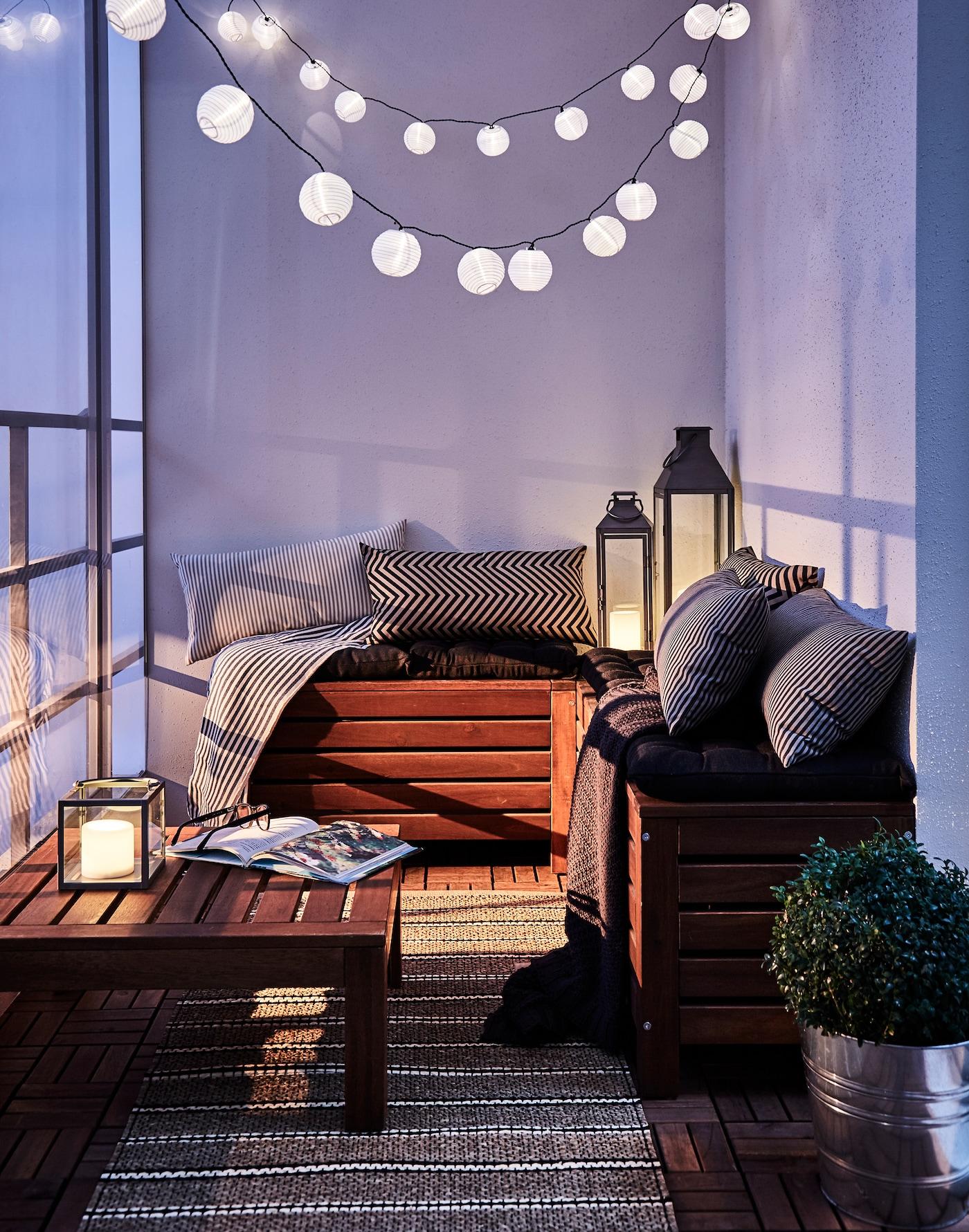 Gemütlich eingerichtete Balkonecke mit Lampen, Laternen, ÄPPLARÖ Holtztruhe & vielen Kissen.