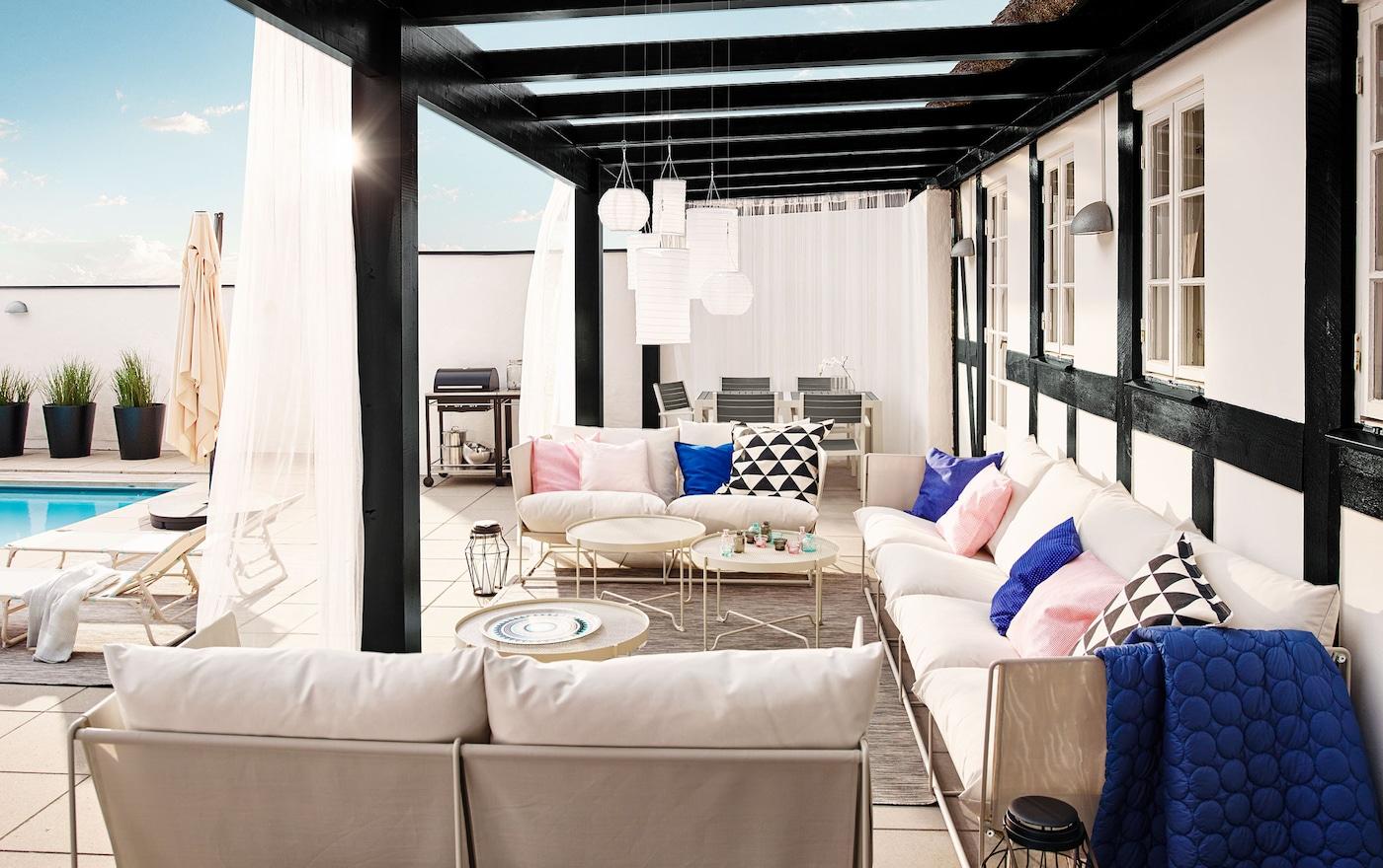 Gemütliche, beige HAVSTEN Sofas für drinnen & draußen unter einer überdachten Terrasse im Garten