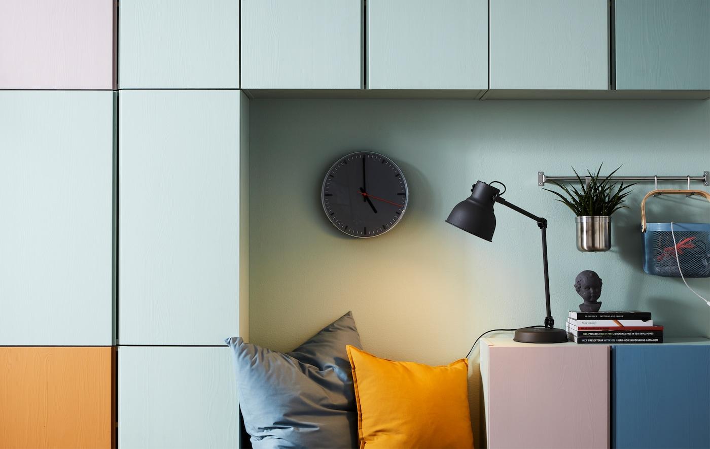 Gemütliche Leseecke mit Wanduhr, Kissen, Lampe & IVAR Regalen, die farblich markiert sind.