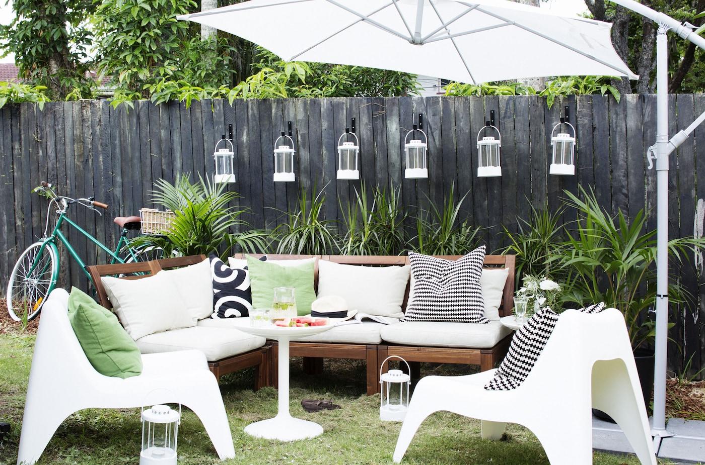 Gemütliche Sitzecke im Freien für Gäste mit IKEA Sesseln, Laternen, Kissen & Sonnenschirm.