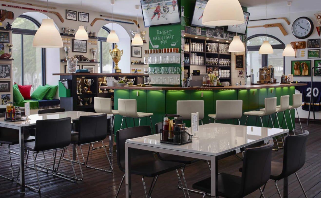 Gemütliche Sportbar mit BERNHARD Stühlen, verchromten TORSBY Tischen, BOTKYRKA Wandregal & Kissen