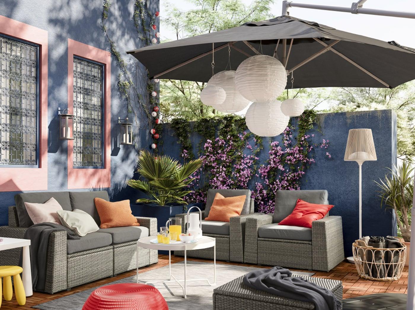 Gemütlicher Außenbereich mit grauen Sitzmöbeln, grauem Sonnenschirm, Pflanzen & Tisch