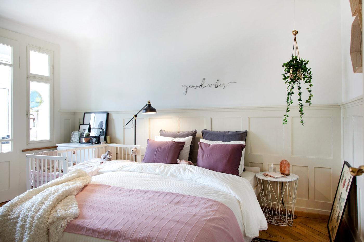 Gemütliches Schlafzimmer mit einem Babybett neben dem Elternbett. Die IKEA RANARP Standlampe sorgt für eine gute Atmosphäre.