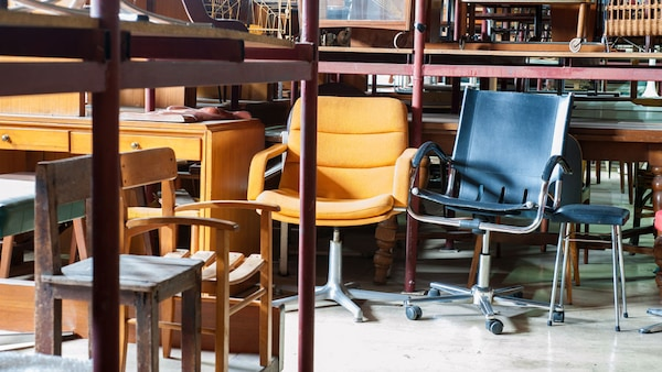 Gently used furniture such as chairs inside a warehouse, along with a message that reads: $25 off coupon when you donate furniture or electronics on November 28th.