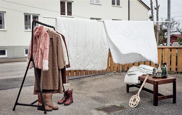 Gepflasterter Vorgarten, der für den Frühjahrsputz hergerichtet ist: Bettdecken hängen über einer Leine zum Lüften, daneben stehen ein Kleiderständer, Schuhe, Textilien und Putzzubehör.