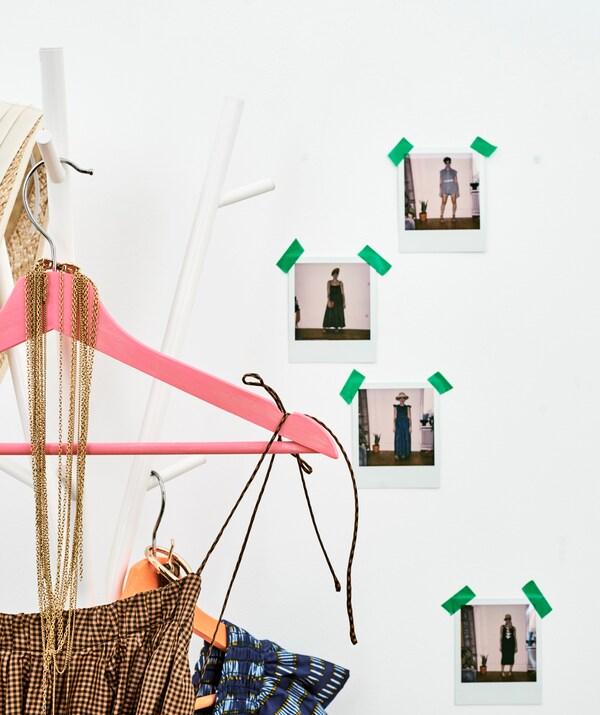 Geruite zomerjurken op kleurrijke hangers hangen aan een kapstok nabij een muur waaraan foto's van vrouwen in verschillende tenues zijn gekleefd.