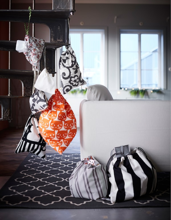 Geschenktüten aus unterschiedlichen grafisch bedruckten Stoffen, u. a. aus MATTRAM Meterware in Orange, sind an einer Wendeltreppe aufgehängt und liegen auch auf dem Fußboden.