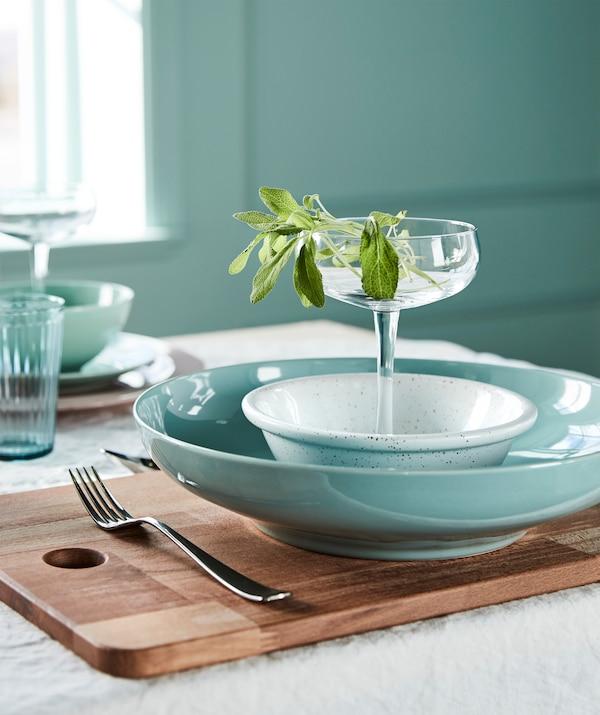 Gestalte einen sommerlichen Tisch mit einer Mischung aus hellen Grün- und frischen Weisstönen. Wir empfehlen hellgrünes Geschirr, wie z. B. die IKEA ENTYDIG Schüssel in Hellgrün auf PROPPMÄTT Schneidebrett aus Buche.