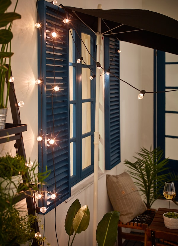 Ghirlande UTSUND cu LED, negre, de la IKEA , aranjate pe peretele unui balcon, în timpul nopții.