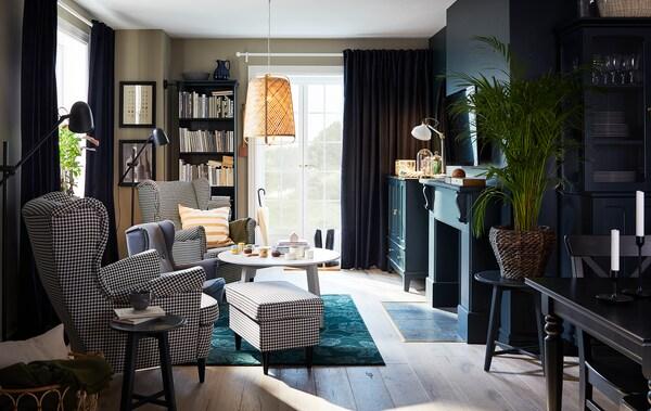 غرفة الجلوس مع اثنين من الكراسي بظهر مرتفع وجوانب بارزة بنقش مربعات، وسجادة خضراء، ومصباح معلق من الخيزران وطاولة قهوة مستديرة.