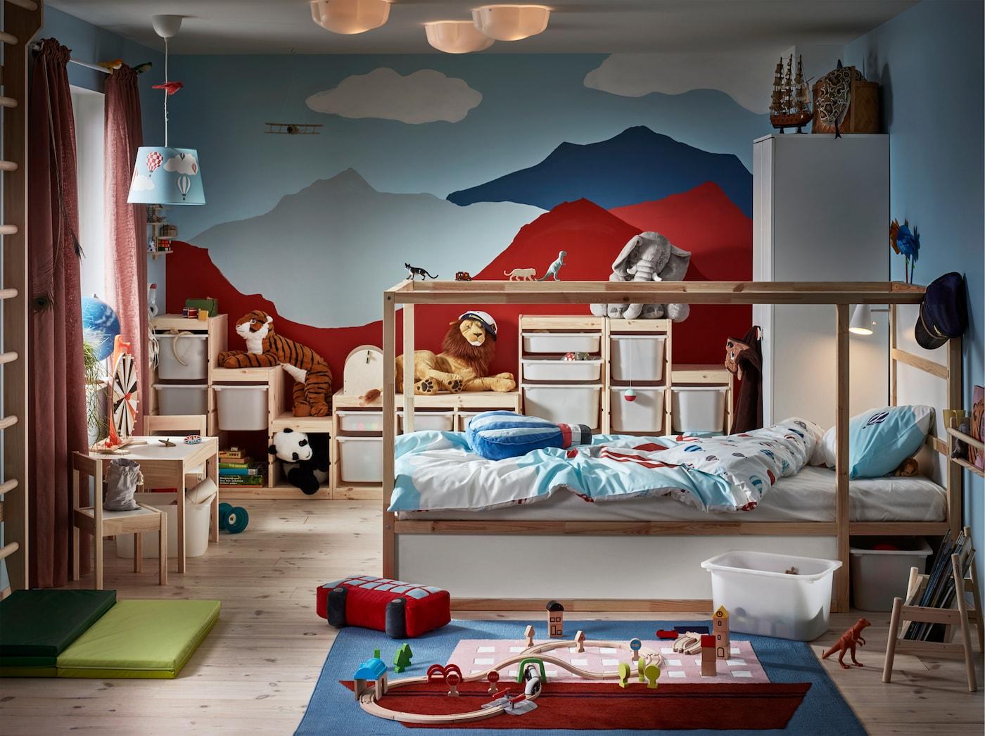 غرفة أطفال بها سرير من خشب الصنوبر وجدار مطلي كالجبال وسجادة عليها رسمة قارب والكثير من الدمى الطرية.