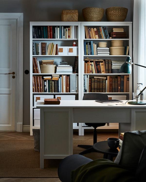 غرفة بها مكتب HEMNES أبيض ومكتبات متوافقة موضوعه خلفه مع سهولة الوصول إليها، مع كتب وصناديق وتخزين زخرفي.