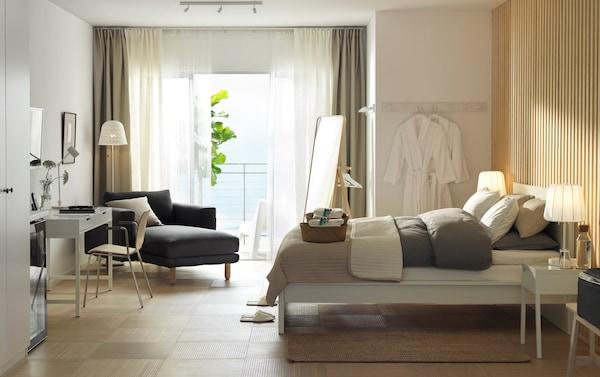 غرفة فندق ذات جدران بيضاء وخشبية مع إطار سرير مالم أبيض من ايكيا، ومكتب أبيض، وأرائك مطلة على البحر.