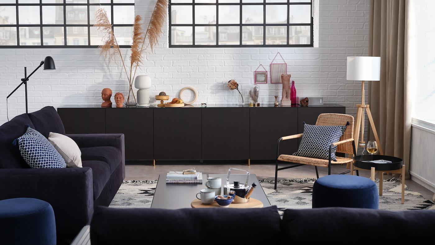 غرفة جلوس أنيقة مع صوفا3 مقاعد وصوفا مقعدين وتشكيلة تخزين مع أبواب وكرسي بذراعين.