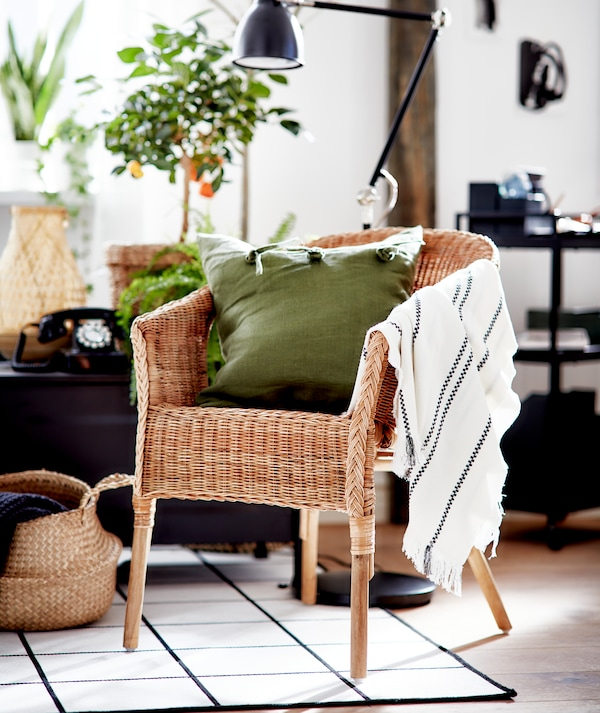 غرفة جلوس باللونين الأبيض والأسود مع لمسات من الخامات الطبيعية وكرسي من الروطان AGEN مع وسادة خضراء.