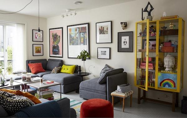 غرفة جلوس بها كنبة وحدات رمادي ووسائد ملونة.