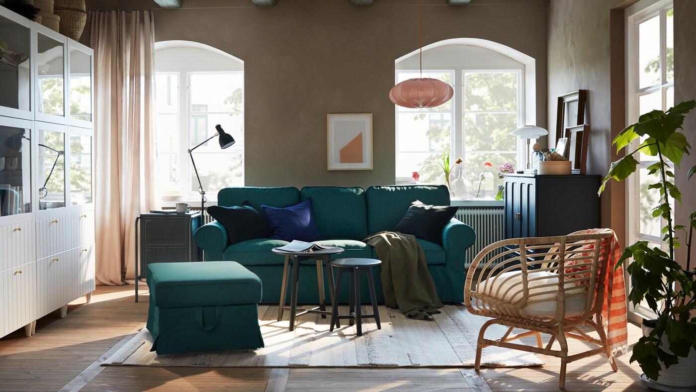 غرفة جلوس بها صوفا ومسند أقدامفيروزي داكن، وتشكيلة تخزين بيضاء وخزانةأزرق داكن-أخضر.