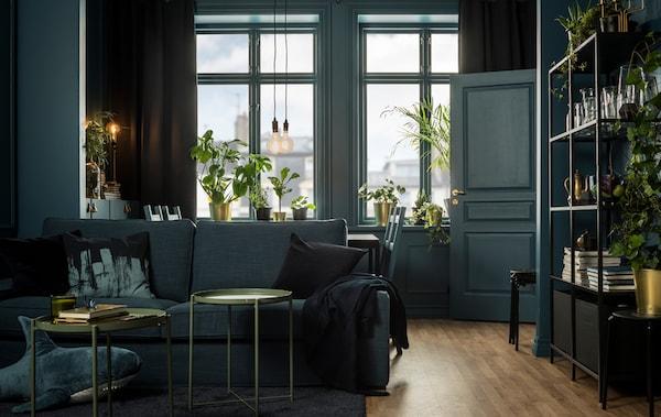 غرفة جلوس بمجموعة ألوان الأخضر العميق، والذهبي والأسود، مزينة بصوفا ومساحة جلوس.